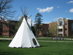 A teepee created by some students. In the background, a class is taking place.